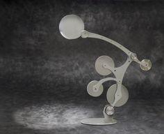 Lampada scultura interamente realizzate in alluminio anodizzato, ha un sistema di carrucole e contrappeso che le permettere cambiamenti di stato rimanendo sempre perfettamente bilanciata. Lampada alogena 70w o a led.