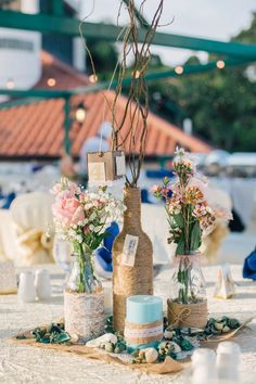 Twine, lace, burlap and mismatched vessels make for infinitely chic table centerpieces / http://www.deerpearlflowers.com/twigs-and-branches-wedding-ideas/