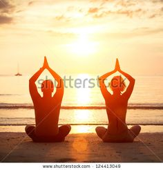 Yoga practice, young couple sitting on the beach of the sea in the lotus position at sunset. - stock photo