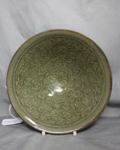 Chinese Celadon Bowl, with a slightly flared lip above a tapering bowl, carved with figures of boys amongst leafy scrolls, in a dark olive green, the whole on a circular foot, d 18.5cm