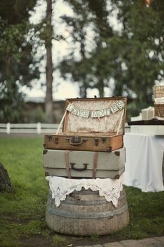 a touch of shabby chic ~ love the old suitcases (perhaps to hold rolled napkins/silverware) sitting on old cut barrel with white doily