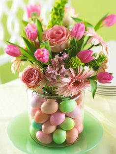 "Easter Egg Vase. From Better Homes and Gardens: ""Start with a large-mouth clear cookie jar or canister and place a clear drinking glass in the center. Gently stack dyed, hard-cooked eggs between the glass and jar, alternating egg colors. Fill the glass with water. Cut the stems of your favorite flowers (we used roses, gerbera daisies, tulips, hyacinth, and bells of Ireland) to the desired length, and arrange them in the glass."" Could also do with plastic eggs."