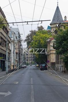 image of a street with overhanging wire. - Image of an empty road with overhanging wire.