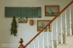 Wall arrangement: framed collection of paint by numbers and shutter coat hanger.