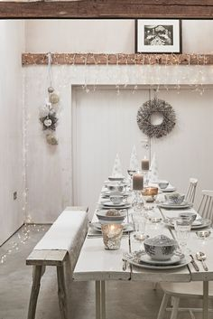 Sainsbury's Autumn/Winter & Christmas Press Show 2015: Dining Room: Christmas Country Retreat - Rustic white wooden benches and worn table, delicate hanging fairy lights, silver entwined twig wreath, metallic candle holders, metal Christmas tree cones and floral bowl sets; to set the mood for entertaining your guests this festive season. - #Simplicity #Modern #Space #Bare #Contemporary - #CamronLatestWork