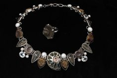 Pyritized Ammonite, Freshwater Pearl, Quartz Drusy Rutilated Quartz, Fossil Shark Teeth make up the components of this fascinating necklace. Pair with Fossil ammonite ring also in sterling silver with hammered texture.