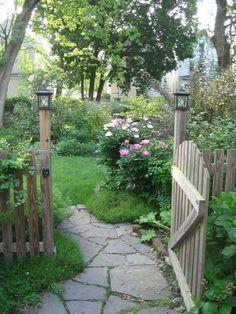 Flagstone pathway through a wooden gate...going into a backyard flower garden area