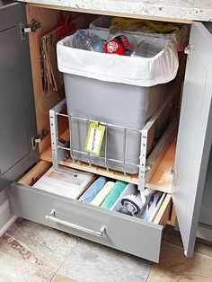 Hide trash and recycling receptacles inside a deep cabinet. Retrofit cabinets with a simple pullout system to accommodate multiple bins.