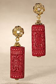 Ornately carved vintage cylinders of rich red Chinese cinnabar, patterned with traditional motifs and medallions, dangle alluringly