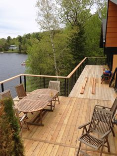 Lake house in Montreal, Canada. Elevated deck update with cable railing system from Stainless Cable & Railing. Black aluminum posts and rail support, cedar top rail, and cable infill.