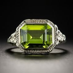 A lively lustrous apple green emerald-cut Peridot glistens and glows from within a beautifully detailed Art Deco era mounting, die-struck and hand finished in two-tone 14K white and yellow gold, circa 1930, ornamented with an artfully stylized heart motif side gallery and orange blossoms on the shoulders (a traditional symbol of love and marriage). Currently a petite ring size 4.