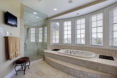 Modern bathroom centered around large window-side tub built into raised tile platform.