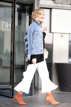 SWAROVSKI – Mi Aventura Con La Moda. Black knit sweater+white ruffled pants+brick red ankle boots+denim jacket+white and gold sequinned chain shoulder bag. Winter To Spring Transition Dressy Casual Outfit 2017