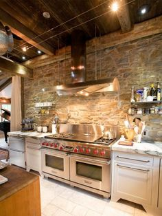 A stone wall is the focal point of this country kitchen designed by Jill Jarrett and Lauren Costar of Jarrett Design, LLC. Professional-quality appliances ensure that the workspace is as functional as it is charming.