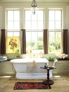 This master bathroom in Senoia, Georgia evokes the opulence of an old-world spa with large soaking tub. Large double-hung windows bathe this space with natural light that's reflected by the honed-marble tile flooring. Cafe curtains provide privacy when drawn, while allowing sunlight to enter from above.