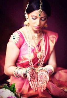 Gorgeous south indian bride in a pink silk saree, traditional jewelry and jhumkas