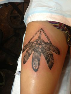 triangles and feathers and eyes thigh tattoo