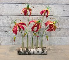 Modern Gloriosa Lily arrangement in artificial in a custom made test tube vase made from a birch log created by our floral designer Joshua Steger. Contact us for your next permanent botanical arrangement. For sale at buds 'n bloom design studio - De Pere - Green Bay, WI www.budsnbloom.com