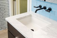 Blue glass tile with beautiful Brizo Faucet water fixture, white marble and sink