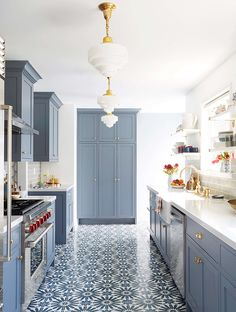 Cornflower blue cabinets brighten grey subway tiles and white walls in this light-filled kitchen, providing a soft counterpoint to the bold patterned tile. | Designer: Emily Henderson