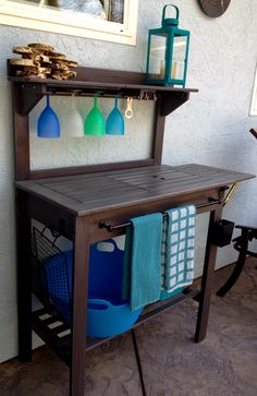 Bought a Potting Bench from Cost Plus World Market...  Added grey stain, towel bar, slots for plastic wine glasses, bottle opener and cap-catcher, side hook and ice/drinks bucket~~  Outdoor Bar now!