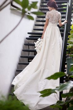 Chantilly lace ball gown wedding dress with a silk faille skirt, embroidered high-neck bodice, and short sleeves by Marchesa | An Exquisite Black and White Styled Wedding Shoot at Da Paolo Bistro Bar