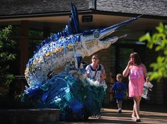 Jacki Butenhoff, Dakota Lowe, 4, and Kaylee Butenhoff look at a sculpture of a Marlin that is made from recycled plastics found in oceans and on beaches around the world during a visit Thursday afternoon to Reiman Gardens in Ames, Iowa. Photo by Nirmalendu Majumdar/Ames Tribune