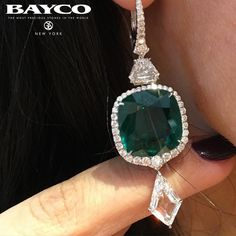 Bayco Jewels. Unique, original kite shape diamond suspended from a magnificent cushion shape Emerald. Photo credit: @luxuryjewelleryevents .