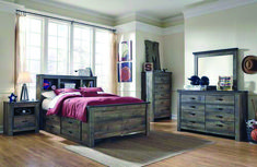 The Trinell bedroom collection is completed in a rustic brown finish over replicated oak grain details for a vintage touch. The bookcase bed features three open shelves on the headboard and two under bed storage drawers. All drawers feature side roll. Trendy Furniture, Furniture Deals, New Furniture, Bedroom Furniture, Bedroom Decor, Adams Furniture, Glam Bedroom, Furniture Direct, Furniture Movers
