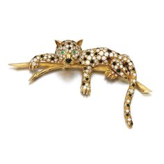 Emerald, onyx and diamond brooch, Van Cleef & Arpels Designed as a panther reclining on a tree branch, set with circular-cut emeralds and onyx and brilliant-cut diamonds, signed Van Cleef & Arpels, numbered, French assay and maker's marks.