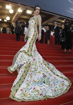 """Fan Bing Bing at Cannes. I LOVE this dress! From AP:   The Chinese actress wore an elegant pale strapless gown by her friend Christopher Bu, decorated with bright floral designs and traditional Ting dynasty stories. Inspired by a porcelain vase, the ancient vibe of her dress was complimented by her hair, which was pinned to look like a young girl from the Tang dynasty.     Fan says she selected the style of these long-gone eras because she didn't want a """"normal, elegant"""" red carpet look."""