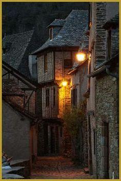 ...Photo à la tombée de la nuit d'une très belle maison à pans de bois et double encorbellement, dans une ruelle encaladée du haut village de Conques,