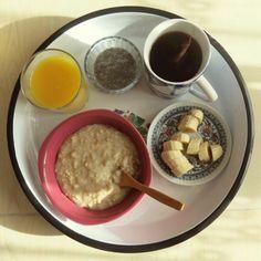 Vegan breakfast with porridge, chia pudding, banana, orange juice and black tea