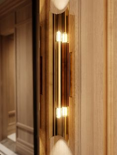 Stunning Brass Curved Wall Sconce and Brass Mirror in oak paneled Powder Room by Toronto luxury home design firm McGill Design Group.