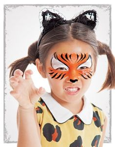 Sponge white face paint around the eyes.  Sponge orange face paint over the cheekbones, nose, and between the brows.  Use a paintbrush to draw tiger stripes on the forehead and cheeks. Paint a small black heart shape at the tip of the nose.  Outline the white paint with black paint. Lace cat ears