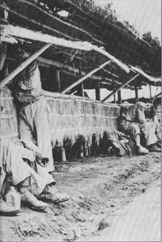 American POWs sit outside one of the barracks at Cabanatuan.