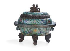 "Very Large Chinese Cloisonne Incense Burner and Cover, early 20th century, of quatrefoil form with a broad flared lip, the body decorated with a dragon and floral design in blue, red, green, yellow and pink enamels, flanked by two bird's-head-form handles and raised on four unusual lion-dog legs, the cover similarly enameled, with a pierced metalwork band of scrolling floral design, surmounted by a horse-form finial, h. 25"", w. 25-1/4"", d. 18-1/..."
