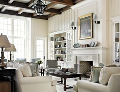 Living room. Living Room sofas are custom with cream quilted velvet upholstery fabric by Fabricut.  Coffee table and end tables are antiques.  The antique wood beams in the living room match the wood floor stain.  Ceiling Height: 14′.