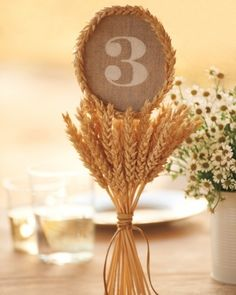 Country Table Numbers  |  Set atop a bundle of wheat, large numerals direct diners to their tables. Linen-covered rounds of cardboard were stenciled with white paint, then placed on a stack of wheat -- the cut ends of which conveniently stand on their own.  |  Rustic Wedding Ideas For Modern Brides via Martha Stewart Weddings(PHOTOS)