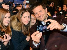 Bradley Cooper works overtime, posing and manning the camera for a fan's selfie at the Paris premiere of American Hustle. http://www.people.com/people/gallery/0,,20782941,00.html#30096480