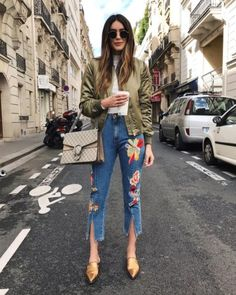 A bomber jacket with a turtleneck, embroidered jeans, and pointy flats.
