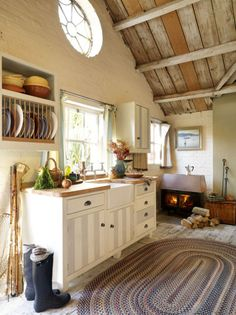 I love everything about this. Beam and plank slanted ceiling, fireplace, striped cabinets, wood counter tops, white and gray, hunter wellies, fresh veggies and flowers, old wood floors. Seriously. I want this.