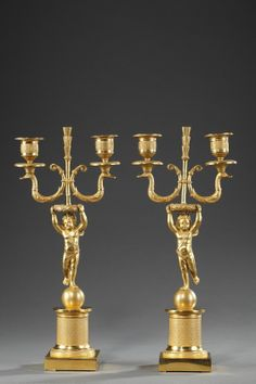 A pair of Restoration gilt and chiselled bronze candelabras, composed of a winged Cupid resting on a sphere and holding a crown surmounted by a swan-shaped two branches torch...