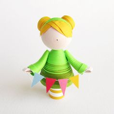 Girl paper art figurine in green with yellow hair buns and banners, quilled paper art sculpture