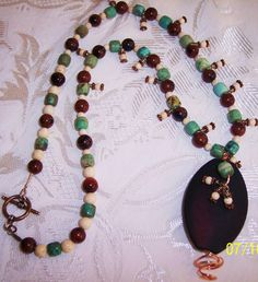 22 inches in length Necklace Bronze Brown focal bead, Turquoise, Brown Obsidian ,and off white River Stone 60.00