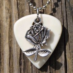 """Our Rose Guitar Pick Necklace is the ideal gift for guitar players, band members, and music lovers. Dangling from a silver-toned, 24"""" ball chain necklace is a guitar pick of genuine cow bone. delicate"""