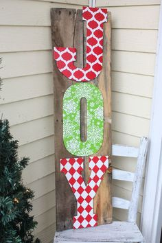 letters, wrapping paper, mod podge, liquid nailed to pallet wood...cheap and cute!