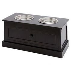 "With a bottom drawer for storage, this timeless wood pet diner features 2 steel bowls and a paneled design for classic appeal.       Product: Pet diner  Construction Material: Wood and steel  Color: Dark brown  Features: Bowls included  Dimensions: 12"" H x 24"" W x 12"" D"