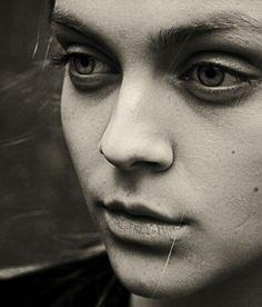 Retrato femenino que mira a la izquierda. Primer plano de joven de ojos azules y mirada perdida.
