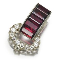 GARNET AND DIAMOND CLIP, CARTIER, CIRCA 1930 Designed as a buckle motif set with 5 baguette garnets weighing approximately 5.00 carats, the buckle set with 11 old European-cut diamonds weighing approximately 1.20 carats, mounted in platinum, signed Cartier, numbered 3817532.